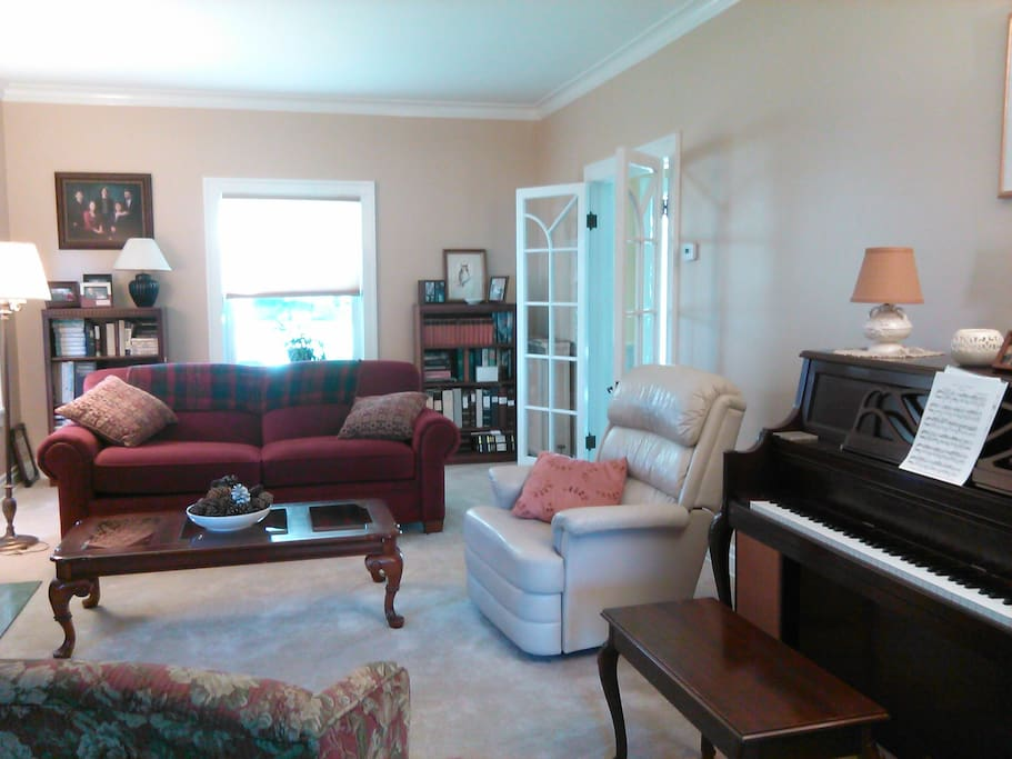 Generous living room features a piano in addition to a television. There is a small den off the side.