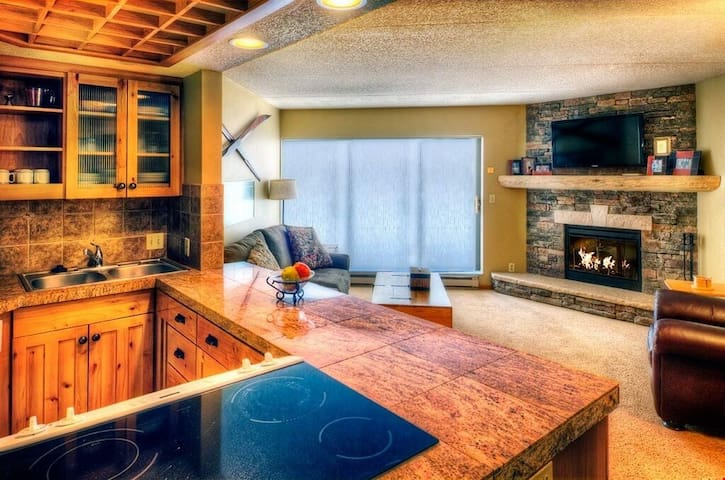 The beautiful stone wood-burning fireplace is the centrepiece for this spacious suite. Photos are representative.