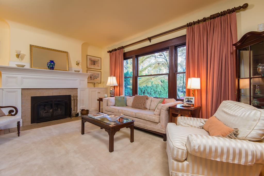 A beautiful formal living room with a gas fireplace and  large screen cable TV.