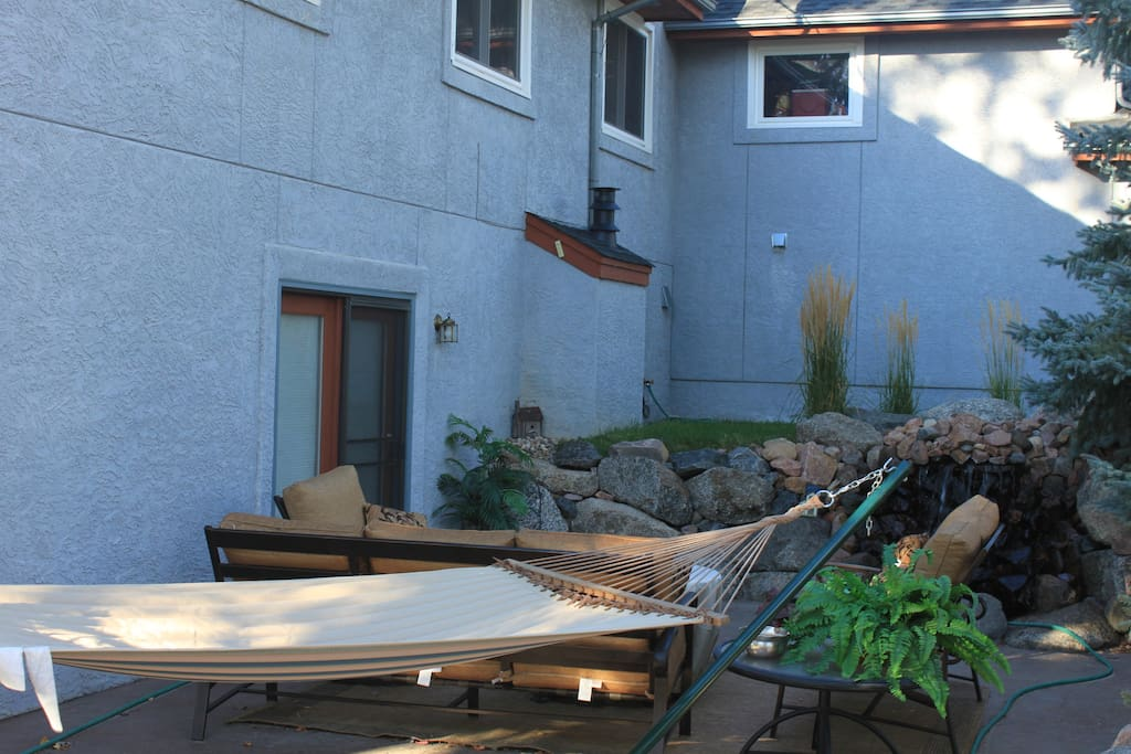 Back patio with fire pit, hammock and waterfall.