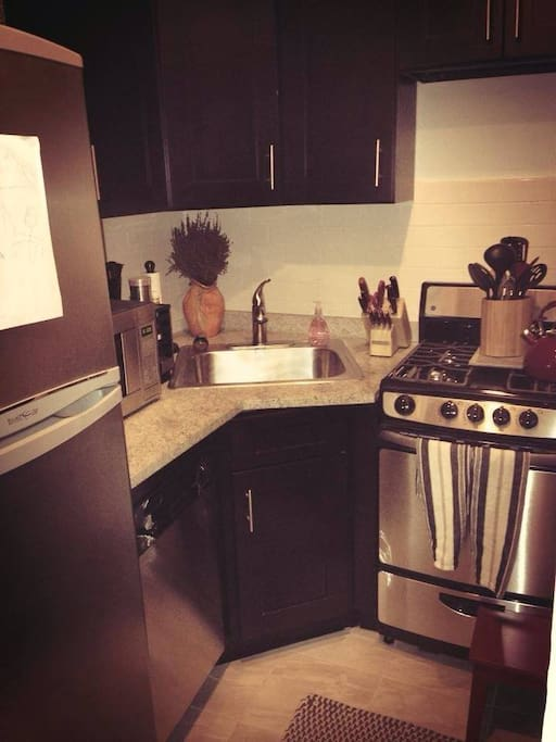 Kitchen with dishwasher, stove, microwave, plates, cups, wine glasses and cooking wear