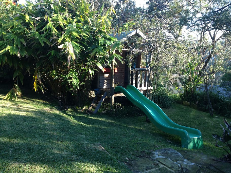 """Outdoor cubby house with indoor kitchen and complete with slide, post box and pulley system for """"packages"""" = hours of fun and entertainment."""
