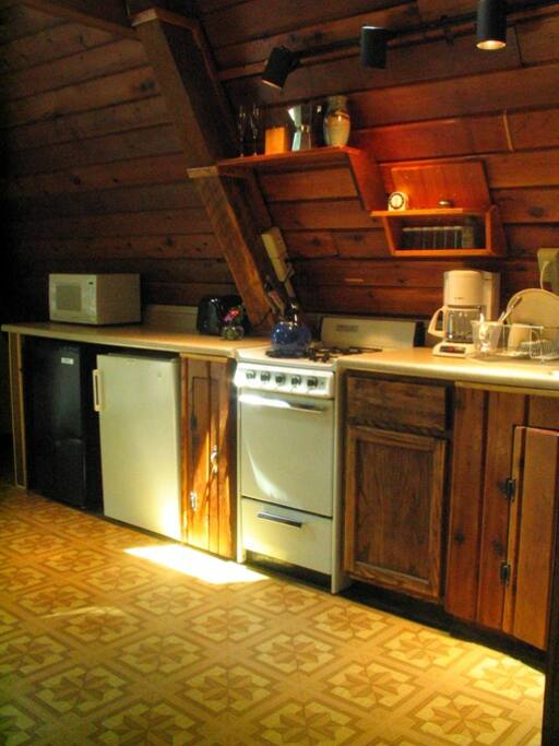Kitchenette is well stocked with modern appliances and cookware.