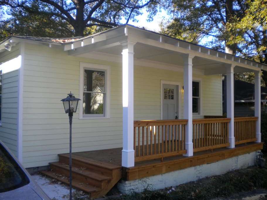 Front of house - with a charming front porch and privacy fence in the backyard.