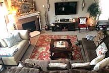 Cozy living room with lots of lounging space, smart TV and gas fireplace.