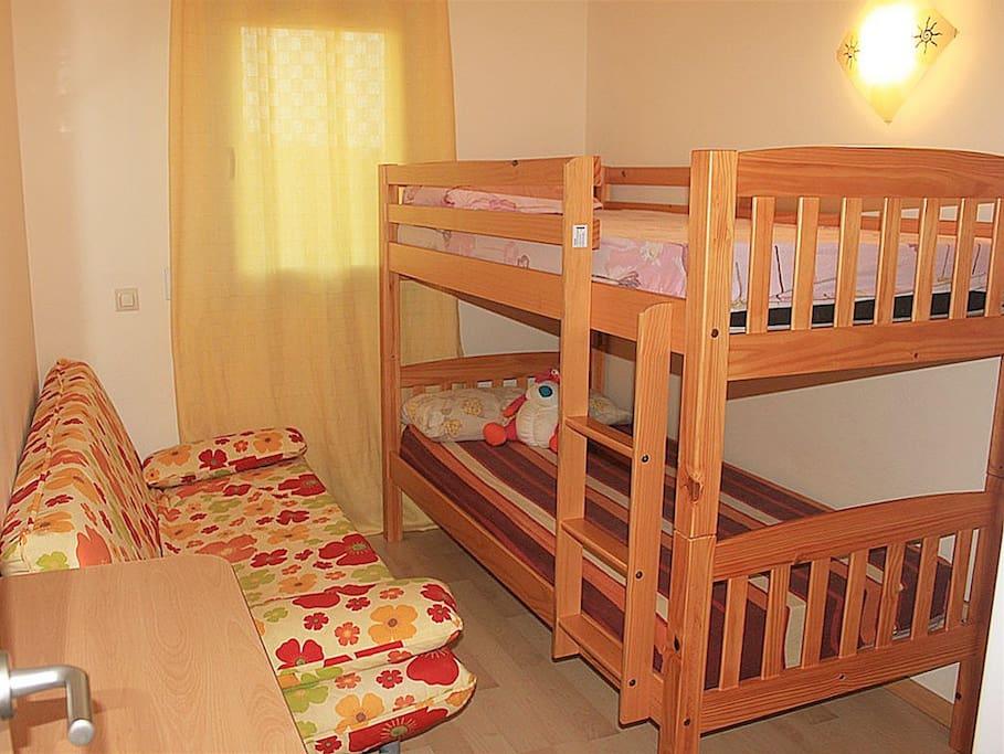 Un dormitorio con sofá cama y cama de dos pisos.