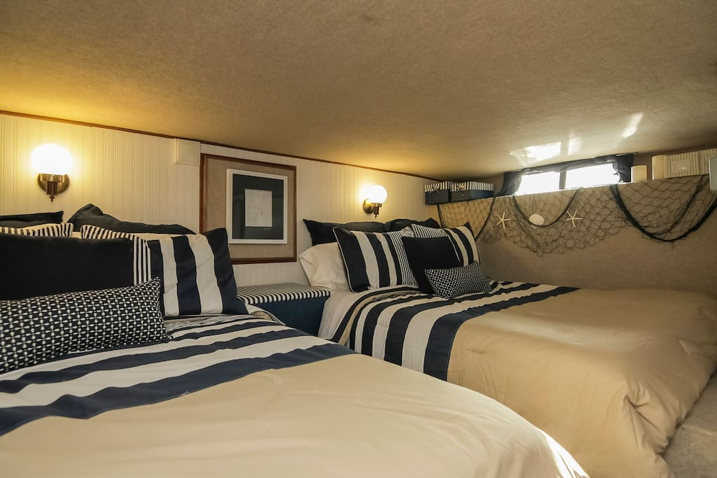 Below deck bedroom with two double beds, half bath.