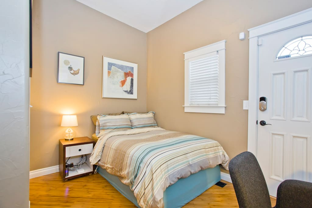Private room located just off the front room - with queen sized bed, closet with storage shelving and hangers, washer and dryer, and desk workspace.