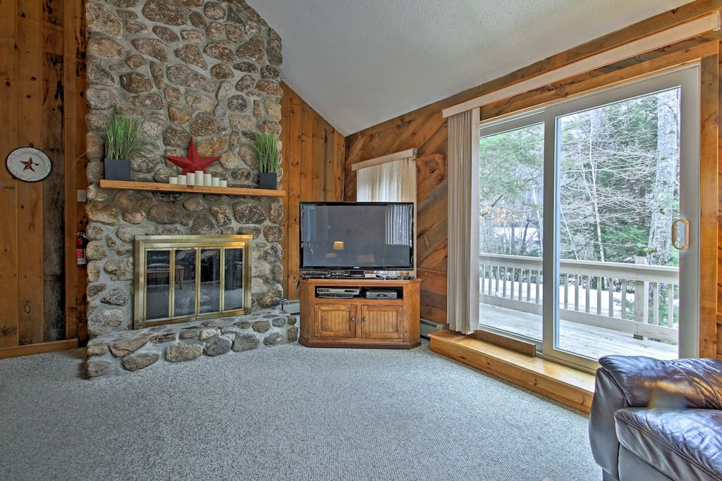 The floor-to-ceiling river rock gas fireplace enhances the cozy alpine ambiance.
