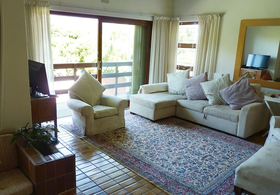 Comfortable lounge, - room for the family to watch DSTV and chill out, with sliding doors leading out onto the balcony.