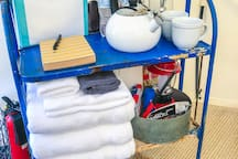 Guest amenity cart with fresh towels, camp lantern, kettle and coffee supplies, board games, and more for your perfect glamping getaway!