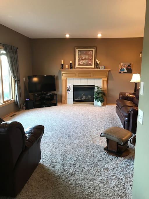Family room has spacious seating with 2 couches, reclining chair, large windows, and gas fireplace