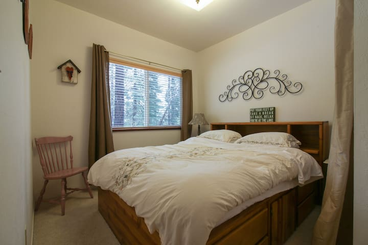 Private bedroom with a queen bed, closet, and window that overlooks the backyard and acres of National Forest.