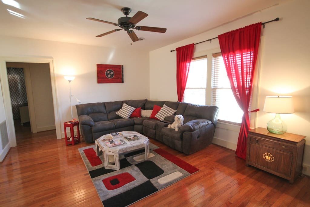 Open living room space with an L-shaped couch, TV, DVR and cable with premium channels.