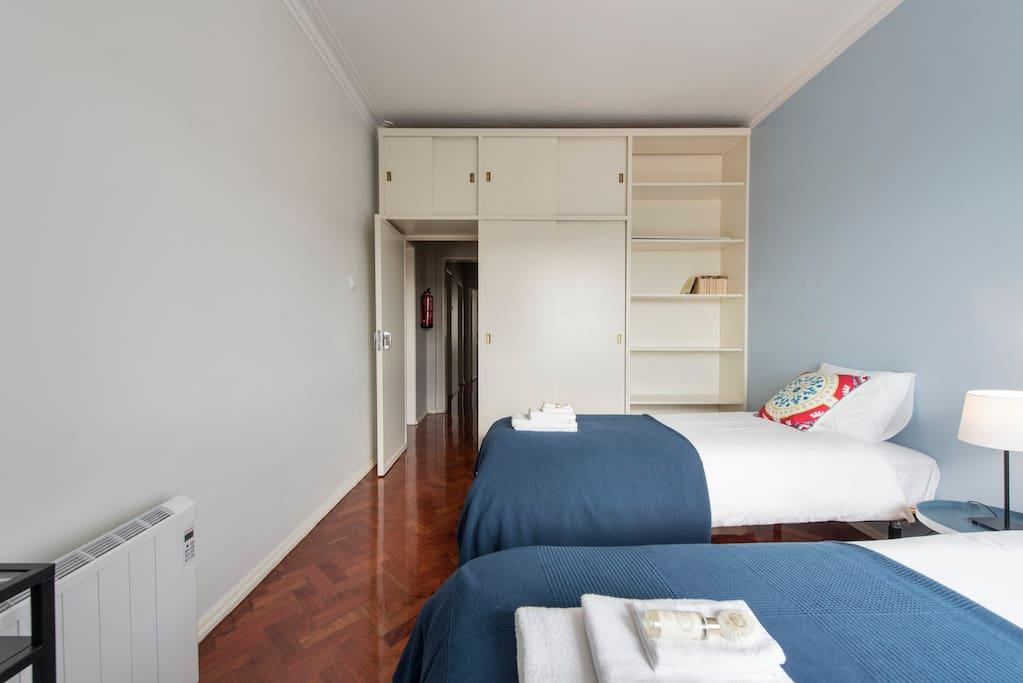 Bedroom with two single beds, labtop desk and wardrobe. It is possible to join then to make a double bed. Quarto com duas camas individuais, secretária para portátil e guarda-roupa. É possível unir as camas numa cama de casal.