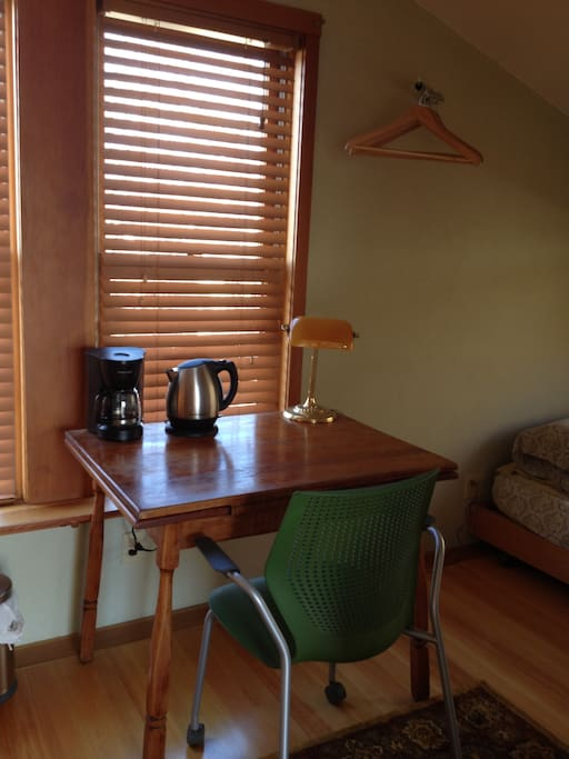 Table with a comfortable Knoll chair provide a great spot for reading and writing or having breakfast; coffee pot and electric kettle for hot beverages.