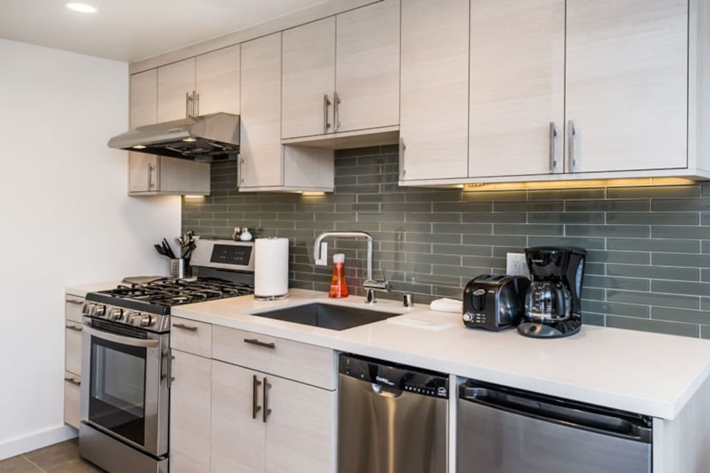 New Stainless Steel appliances, white stone counters & glass tile backsplash.
