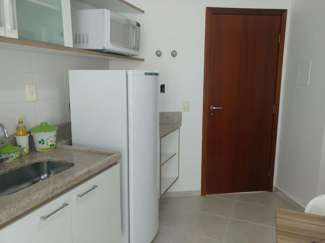 Cozinha com fogão cooktop, pia, arm