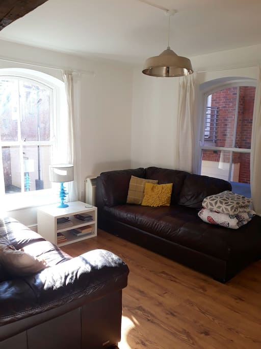 Living area with 2 very comfy large leather sofas, warm fluffy blankets, wooden table with 4 chairs and 2 beautiful sash windows