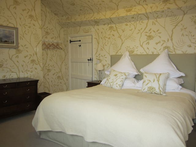 Super king sized bed with lots of pillows and cushions to admire the view of Hergest Ridge through the window