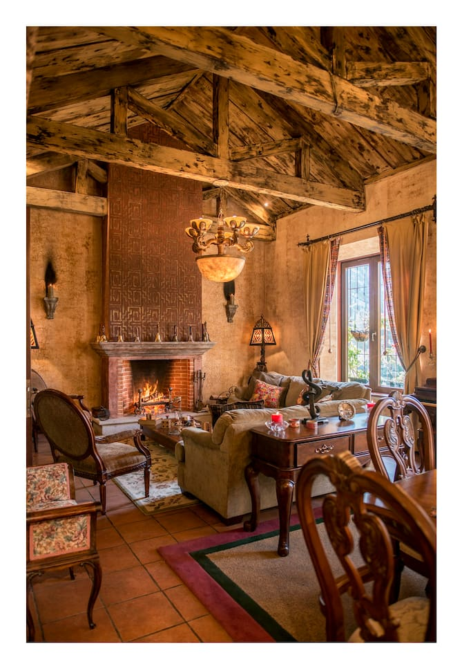 Gorgeous living room to relax with chimney, antique piano and table games.