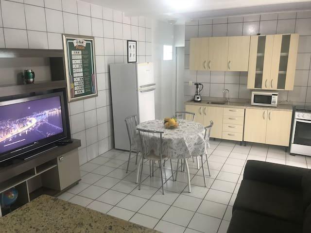 Sala e cozinha  particular, com ar condicionado no ambiente.