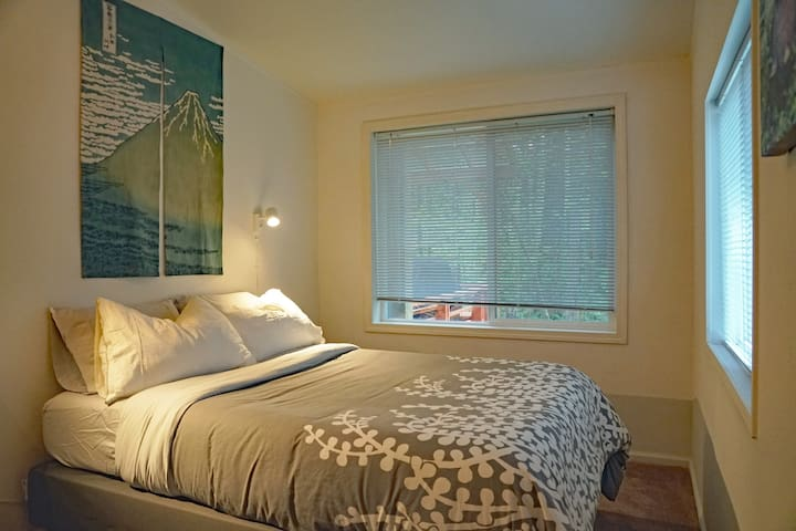 Guest bedroom #3, cozy with views of the woods from both large windows. Or keep the shades closed for darkness.