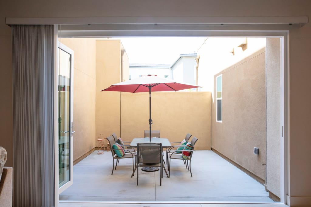 Large private patio features a large umbrella, table, and seating for six.