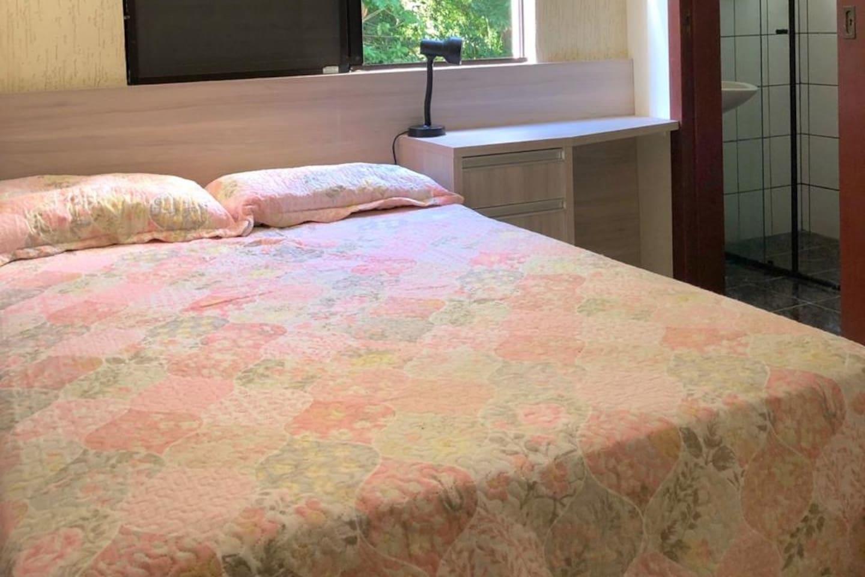 Quarto suite privado com cama de casal, ambiente arborizado e com barulho de cachoeira.