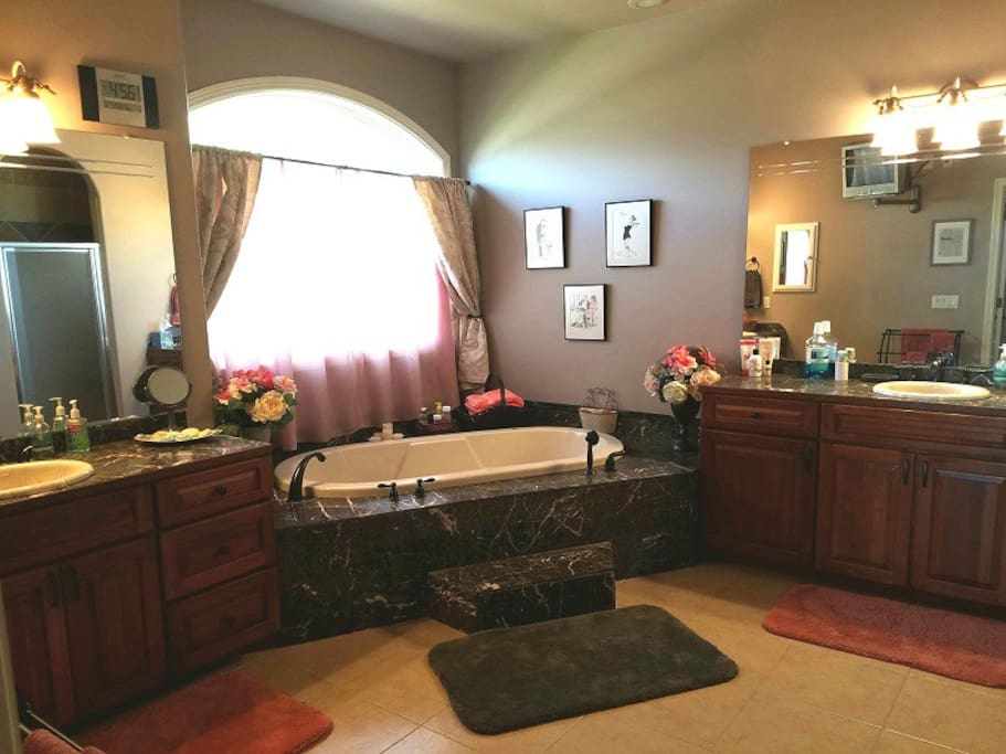 Master bath with dual vanities, jetted garden tub, toilet, and shower