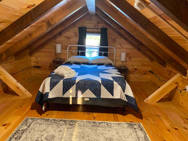 Loft Bedroom with a Queen Bed.  Center of loft is over 6' tall and the sides taper down.  You can access the bed from the foot of the bed or you can access from the sides with some bending.