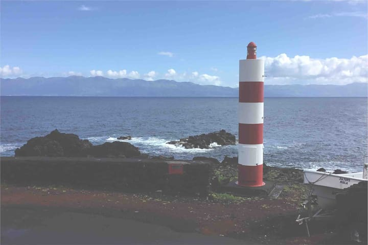The Majestic Lighthouse of Prainha de Baixo- directly in front of the house with Saõ Jorge Island directly ahead.