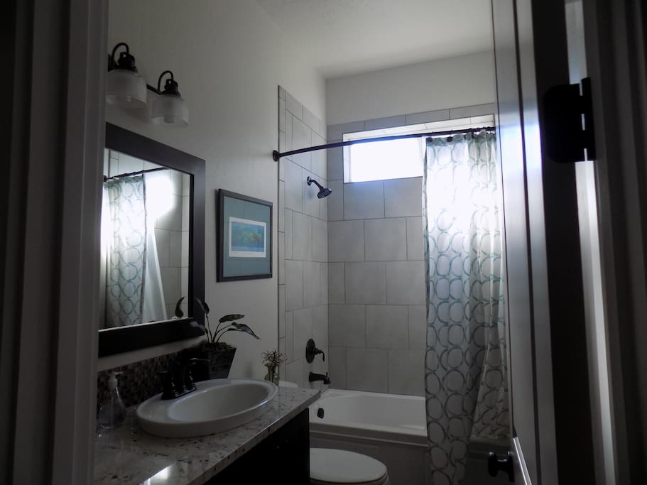 Private bathroom just outside the bedroom that has a bath/shower combo and personal cleaning amenities.