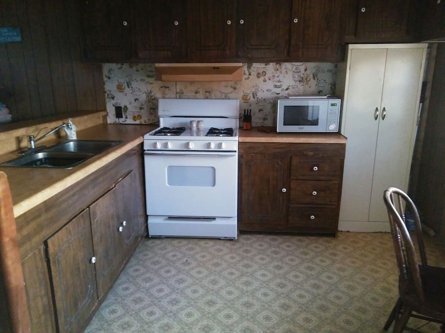 Stove, Microwave, Toaster oven, The metal cabinets have kitchen supplies in them.