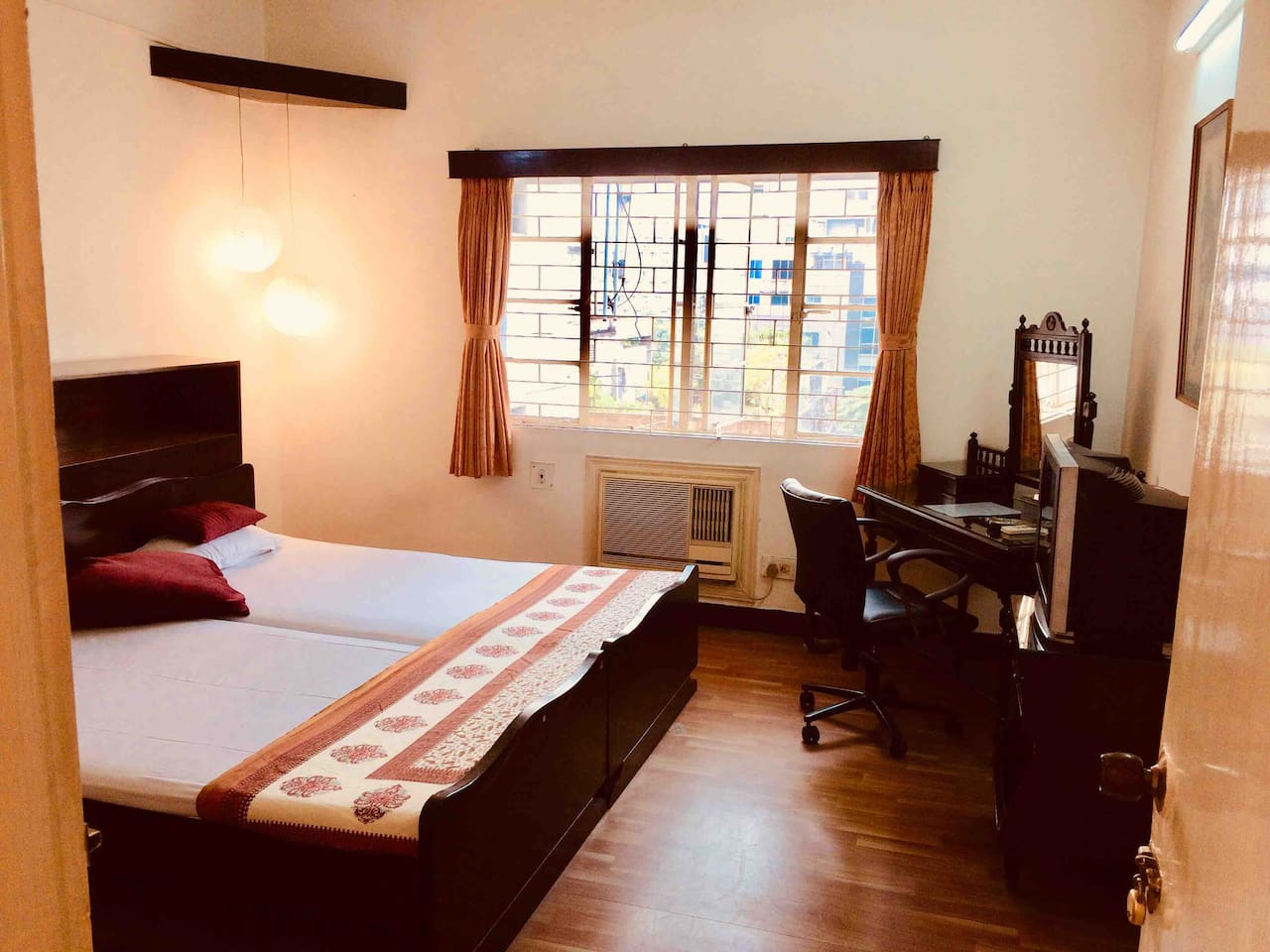 This photo is taken from the main door to Stilt Walker North Private Room. The 2 single beds joined together, a large window, AC (Wall fitting), Antique dressing table which can be used as a writing desk / laptop rest, with a swivel chair for comfort
