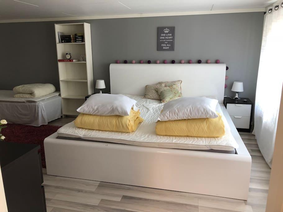 Sovrum med dubbelsäng och två enkelsängar.