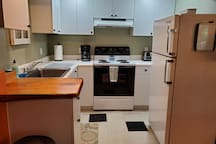 Kitchen equipped with the basics- toaster, microwave, coffee maker & coffee, fridge, and oven