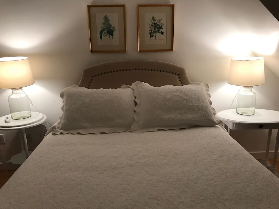 The queen bed with new mattress is outfitted with high quality bedding for a restful slumber.