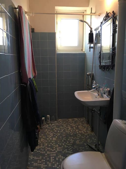 Bathroom with included towels, small window and closing door.