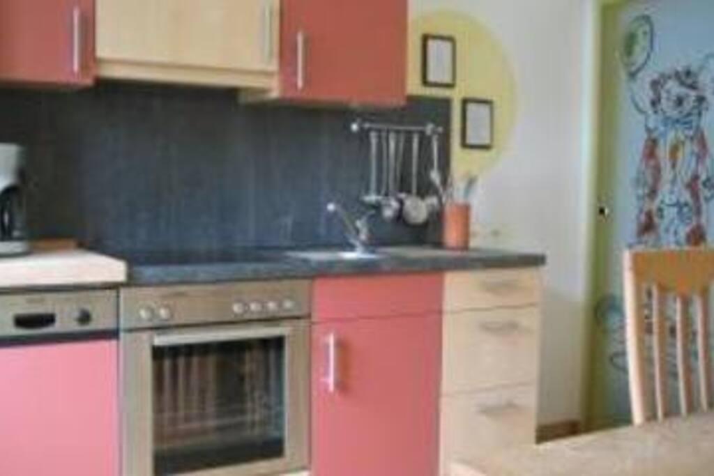 Wohnküche mit Tisch und 8 Stühlen und TV.