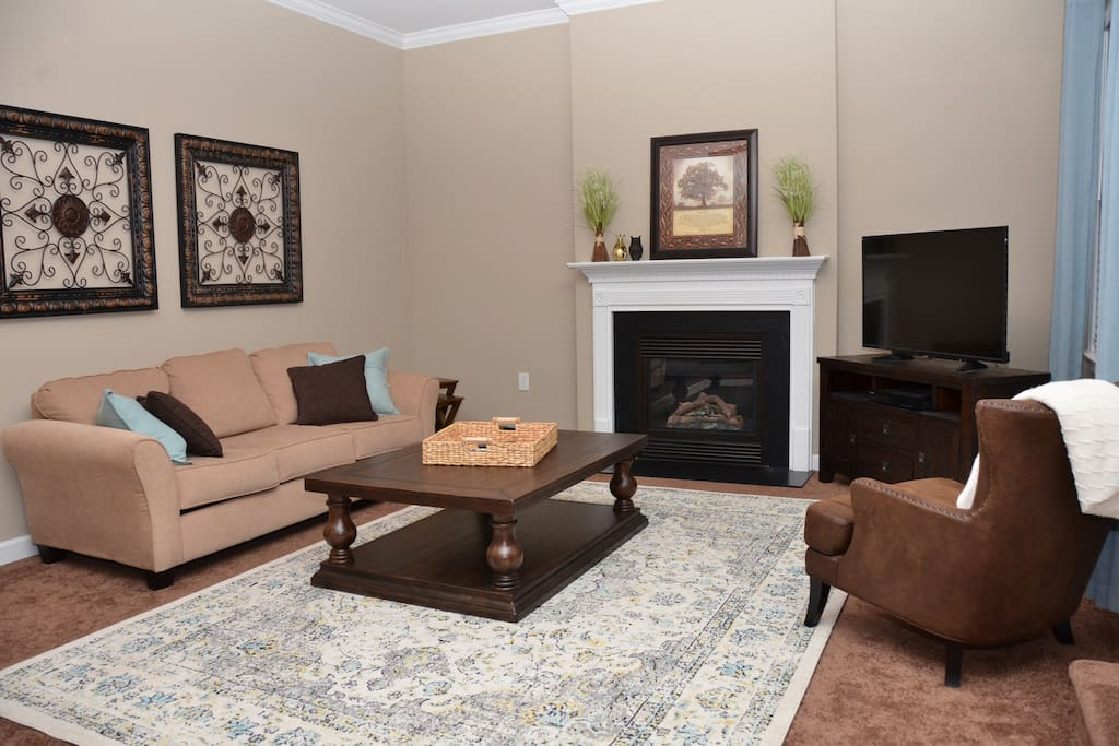 Living room with gas fireplace, ceiling fan and HD TV with Cable DVR.