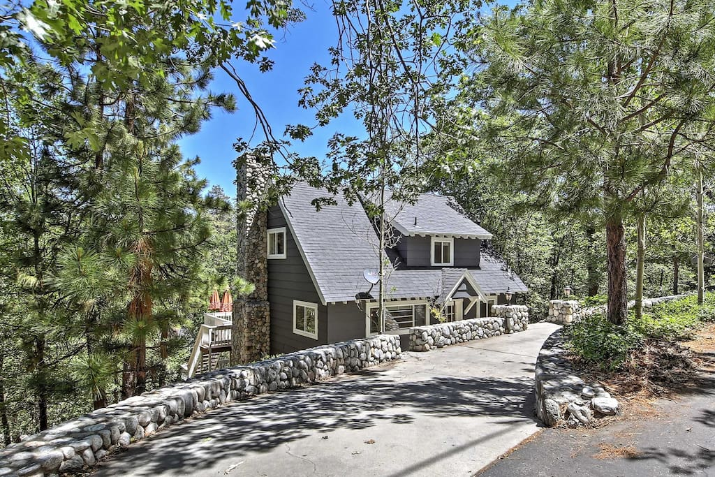 The lovely cottage is tucked below a rock wall and surrounded by towering trees.
