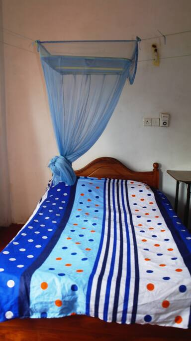comfy double bed with mosquito net and overhead fan
