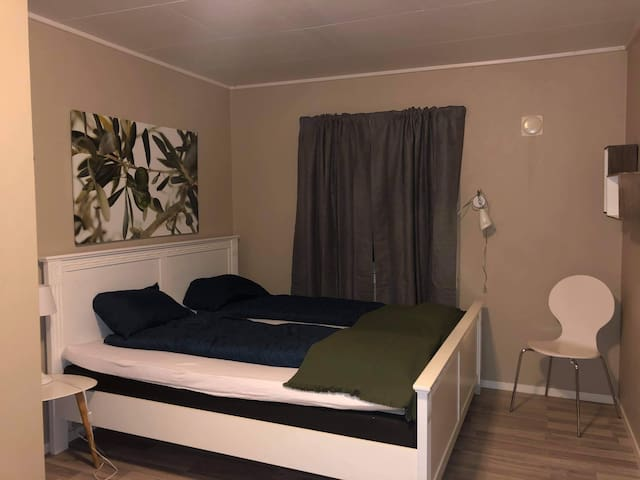 Soverom 1 med 180cm seng og lystette gardiner.