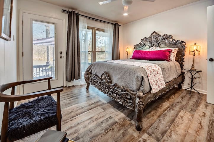 Bedroom with Queen Bed. Rustic handcarved wood stylish & elegant design It's dark oak finish and floral pattern give this bed a special look all its own. Spectacular lake view & private door to access the back deck/porch with seating area.