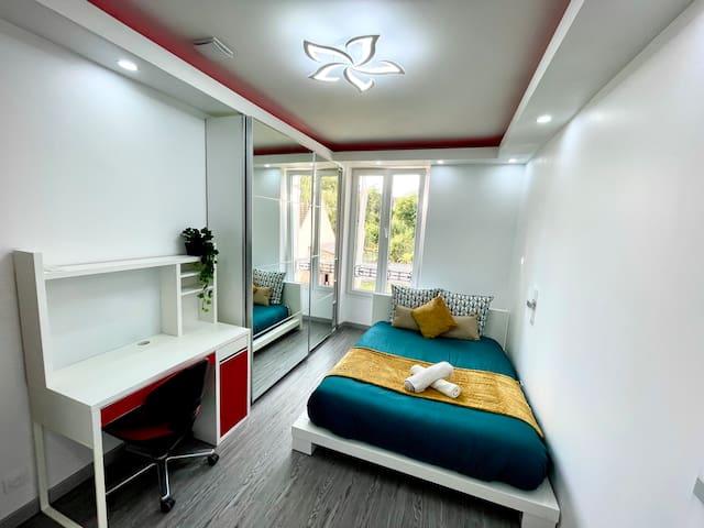 Chambre 2 à l'étage avec un bureau et une grande armoire.