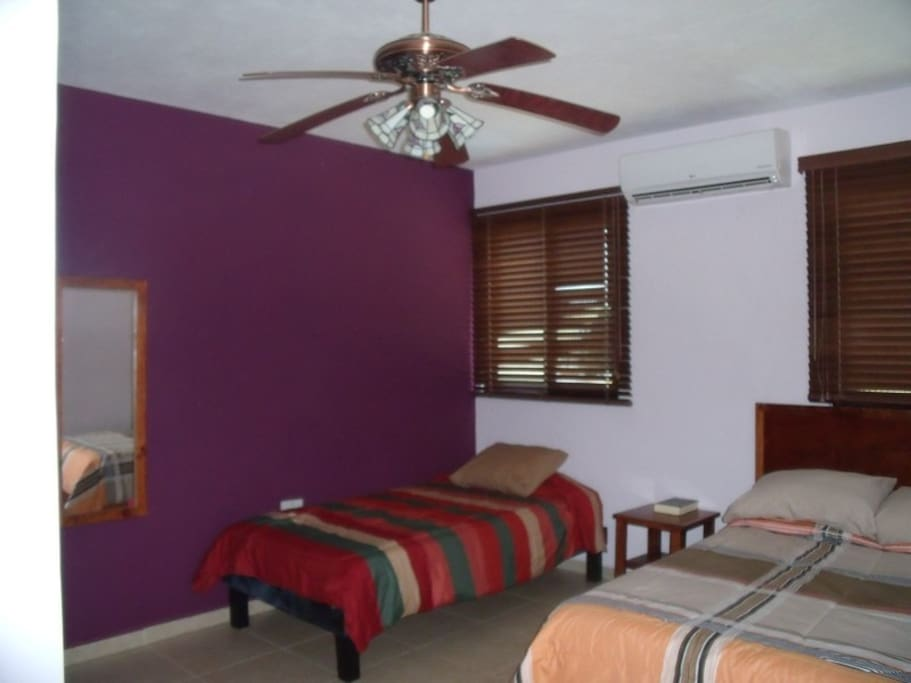 Clean room with air conditioner and ceiling fan.
