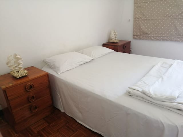 Main bedroom with queen bed, mosquito net over the bed and AC unit. Has a balcony that has a partial sea view.