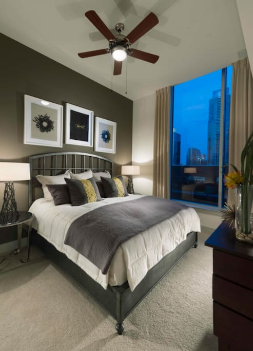 Bedroom with views overlooking the city and a king size bed.