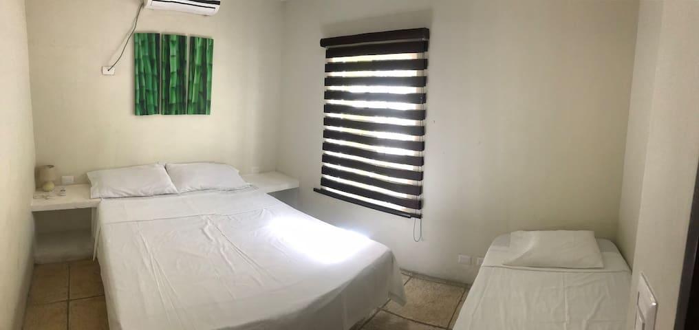 Segundo cuarto de área de abajo con cama queen, cama imperial y aire acondicionado silencioso